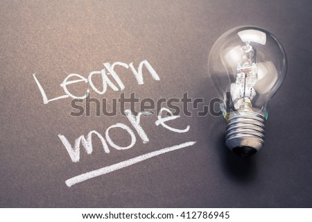 Handwriting of Learn More text with glowing light bulb - stock photo