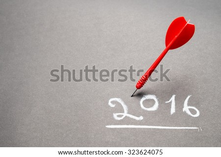 Handwriting of 2016 on chalkboard with dart - stock photo