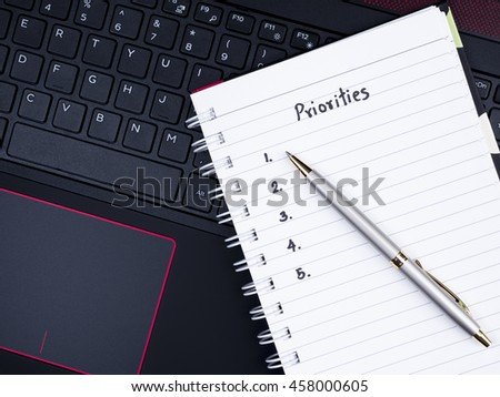 Handwriting Priorities on white notebook and pen with laptop keyboard background (top view) - stock photo