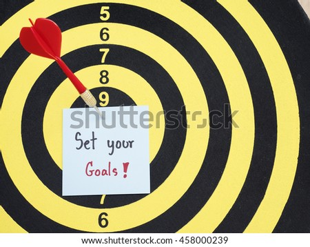 Handwriting Set Your Goals on notepaper with dart arrow and dart board. (Business concept) - stock photo