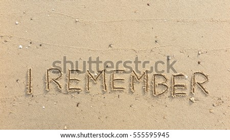 "Handwriting words ""I REMEMBER"" on sand of beach"