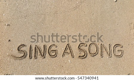"Handwriting words ""SING A SONG"" on sand of beach"