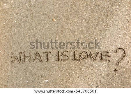 "Handwriting words ""WHAT IS LOVE?"" on sand of beach"