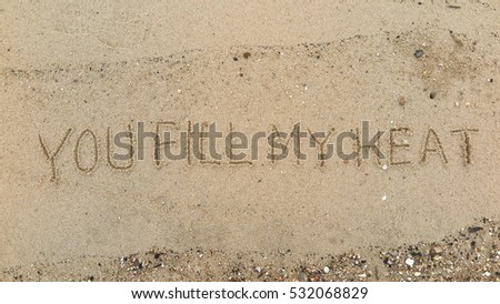 "Handwriting words ""YOU FILL MY HEAT"" on sand of beach"