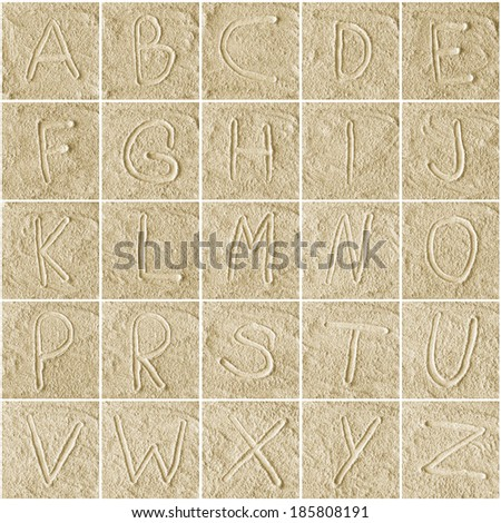 handwritten alphabet letters on sand background - stock photo