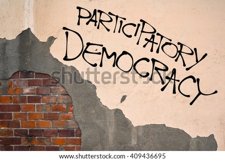 Handwritten graffiti Participatory Democracy sprayed on the wall, anarchist aesthetics. Appeal to participate on democratic decision-making as citizen. Opposition of representative democracy - stock photo