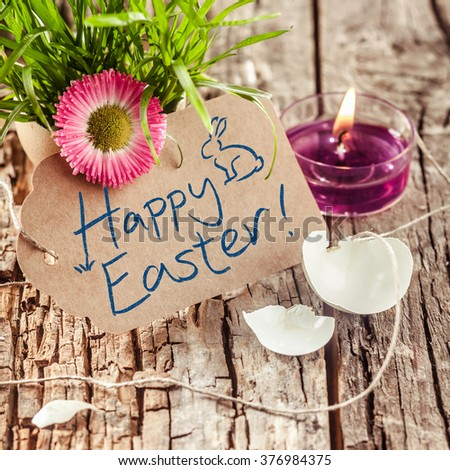 Handwritten Happy Easter wishes or greeting on a brown gift tag with a broken eggshell, fresh grass with a colorful spring flower and burning candle, rustic wood background - stock photo