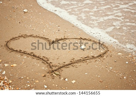 handwritten heart on sand with wave approaching - stock photo