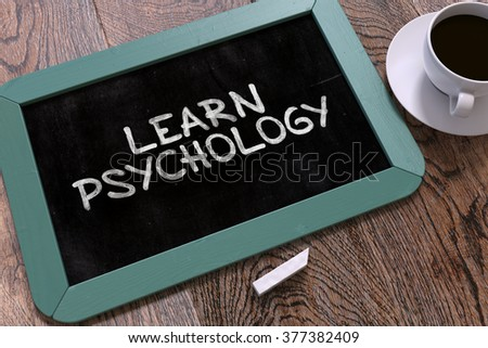 Handwritten Learn Psychology on a Blue Chalkboard. Top View Composition with Chalkboard and White Cup of Coffee. 3D Render. - stock photo