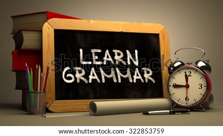 Handwritten Motivational Quote - Learn Grammar - on a Chalkboard. Composition with Chalkboard and Stack of Books, Alarm Clock and Rolls of Paper on Blurred Background. Toned Image. - stock photo