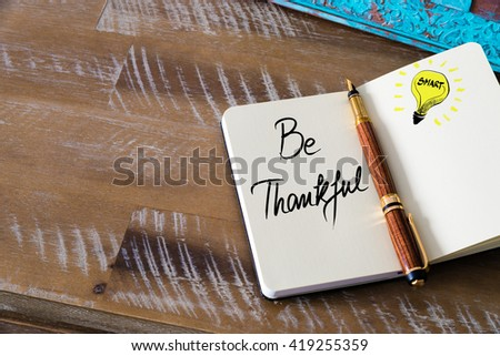 Handwritten text Be Thankful with fountain pen on notebook. Concept image with copy space available. - stock photo