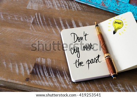 Handwritten text Don't Cry Over The Past with fountain pen on notebook. Concept image with copy space available. - stock photo