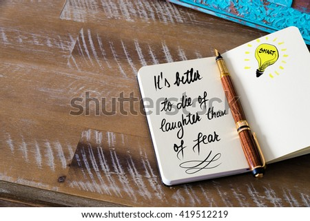 Handwritten text It is better to die of laughter than of fear with fountain pen on notebook. Concept image with copy space available. - stock photo
