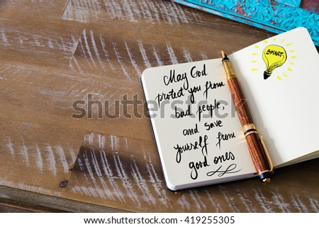 Handwritten text May God protect you from bad people, and save yourself from good ones with fountain pen on notebook. Concept image with copy space available. - stock photo