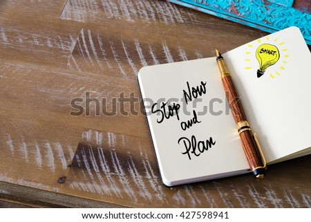 Handwritten text Stop Now And Plan with fountain pen on notebook. Concept image with copy space available. - stock photo