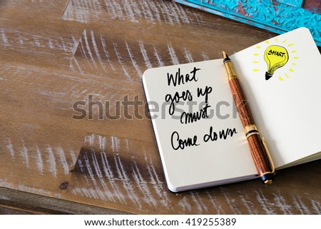 Handwritten text What Goes Up Must Come Down with fountain pen on notebook. Concept image with copy space available. - stock photo