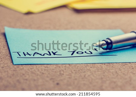 Handwritten Thank You note written on a blue sticky note lying on a cork board with a fountain pen viewed low angle. - stock photo