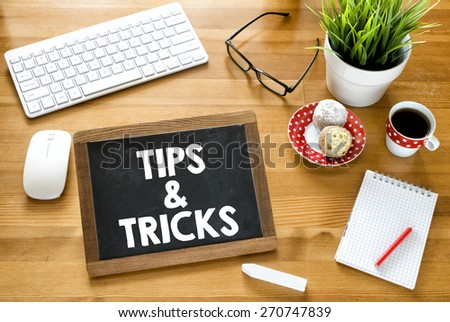 Handwritten tips & tricks on blackboard. Handwritten tips & tricks with chalk on blackboard, keyboard,notebook,glasses,cup of coffee,baking and green plant on wooden background - stock photo