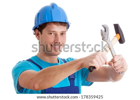 Handy man in blue outfit with hammer and wrench - stock photo