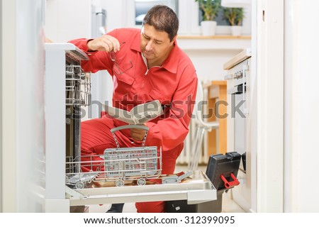 Handy man reading the instruction manual trying to fix the broken dishwasher machine in the kitchen - stock photo