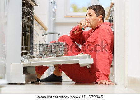 Handy man trying to troubleshoot a problem with the dishwasher in the kitchen. Copy space