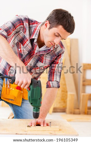 Handyman at work. Confident young handyman working in workshop