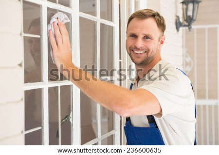 Handyman cleaning the window and smiling in a new house - stock photo