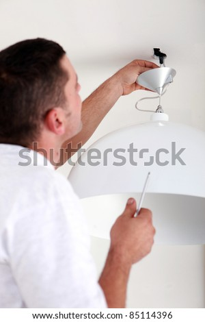 handyman fixate a lamp on the ceiling - stock photo