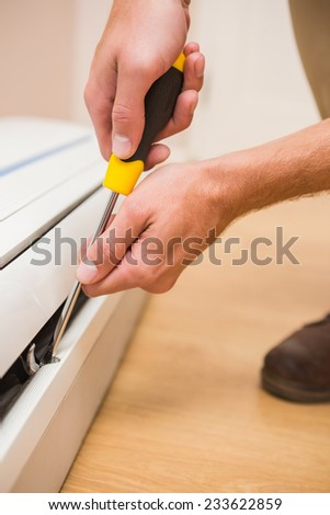 Handyman fixing an air conditioning in a new house - stock photo