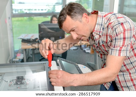 Handyman fixing the office printer - stock photo