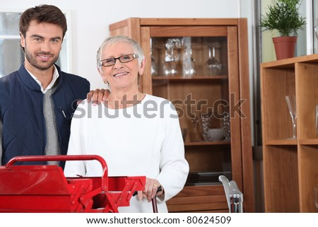 Handyman helping out a senior woman at home - stock photo