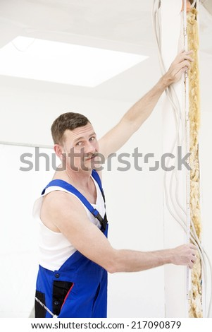 handyman holding a measure tape to a wall - stock photo