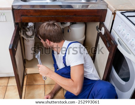 Handyman holding a wrench and sits on the floor - stock photo