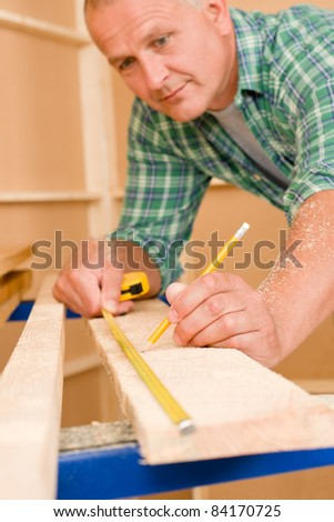 Handyman home improvement close-up of measure wooden board with ruler - stock photo