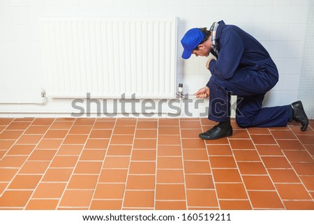 Handyman in blue boiler suit repairing a radiator in bright room - stock photo