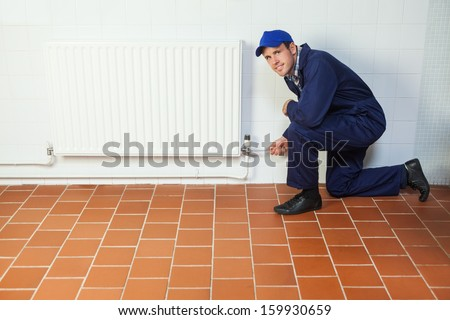 Handyman in blue boiler suit repairing a radiator smiling at camera in bright room - stock photo