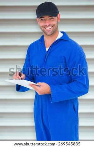 Handyman in blue overall writing on clipboard against grey shutters - stock photo
