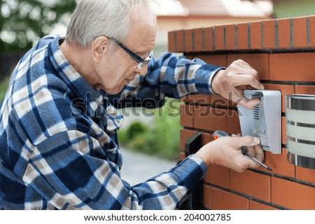 Handyman in flannel shirt fixing intercom, horizontal - stock photo