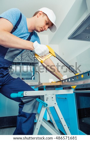 Handyman  in protective professional clothes cutting steel with a hacksaw