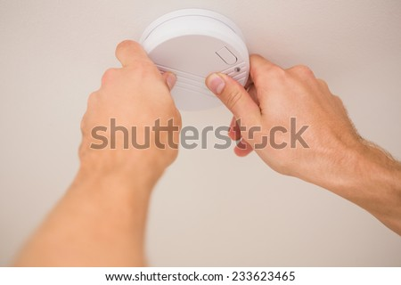 Handyman installing a smoke detector on the ceiling - stock photo