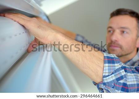 Handyman installing a window shutter - stock photo
