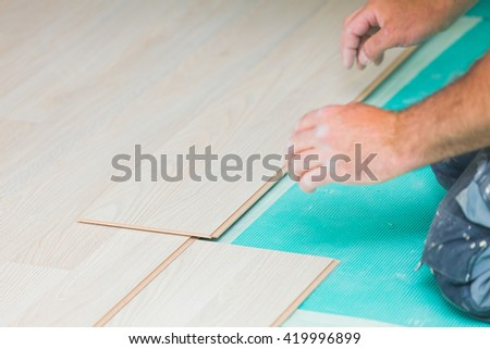 Handyman laying down laminate flooring boards while renovating a house.