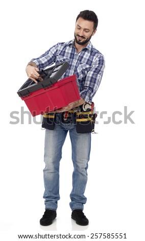 Handyman looking at toolbox - stock photo
