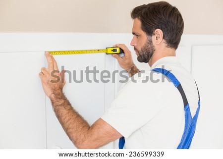 Handyman measuring a wardrobe in a new house - stock photo