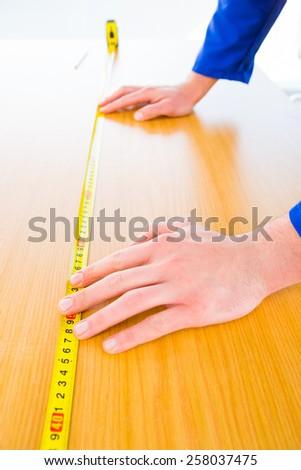 Handyman measuring wood board in bright office - stock photo