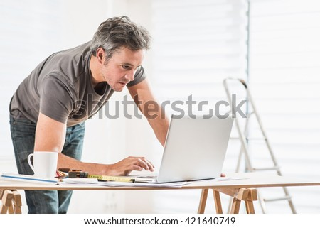 Handyman performing renovation work in a house, he looks at the project on a laptop