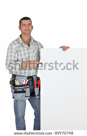 Handyman pointing at blank poster - stock photo