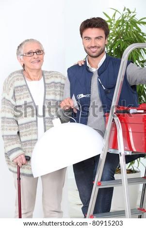 Handyman putting up lampshade - stock photo