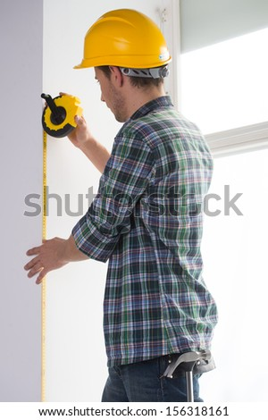 Handyman. Rear view of confident craftsperson in hardhat measuring the wall level