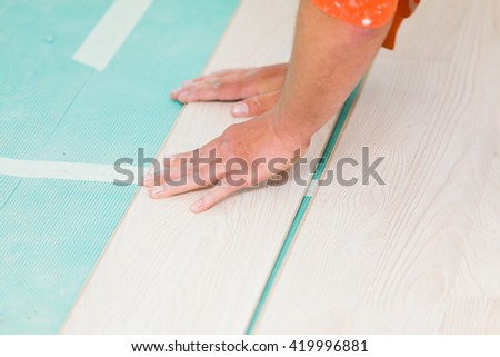 Handyman renovating house, installing laminate wood flooring with care.